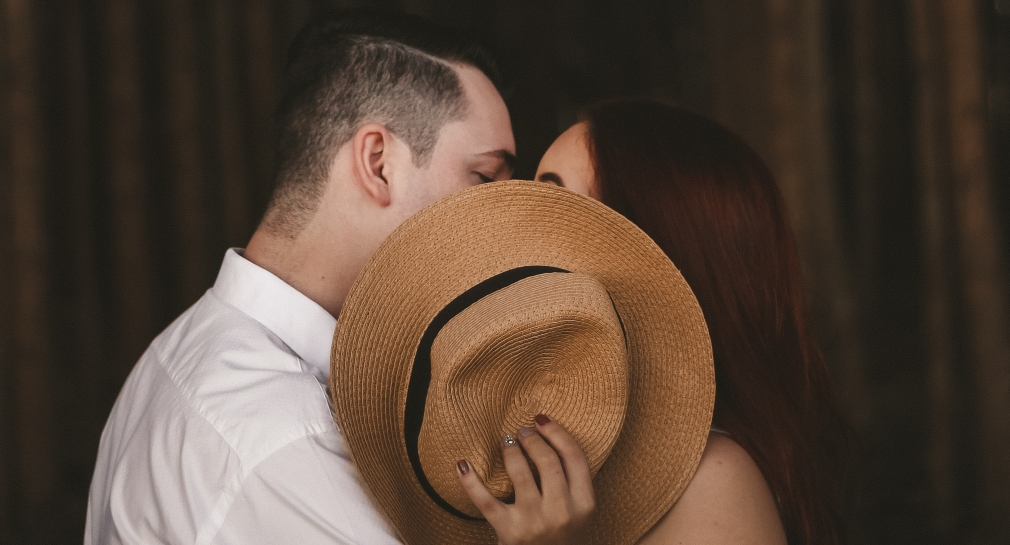 Couple hiding kiss behind hat